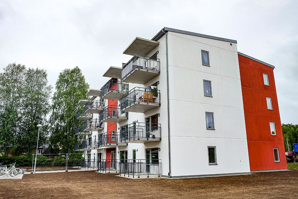 Vitt och rött fyravåningshus i puts