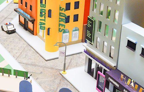 En stad gjord av papp med hus, träd, gator och en polisbil