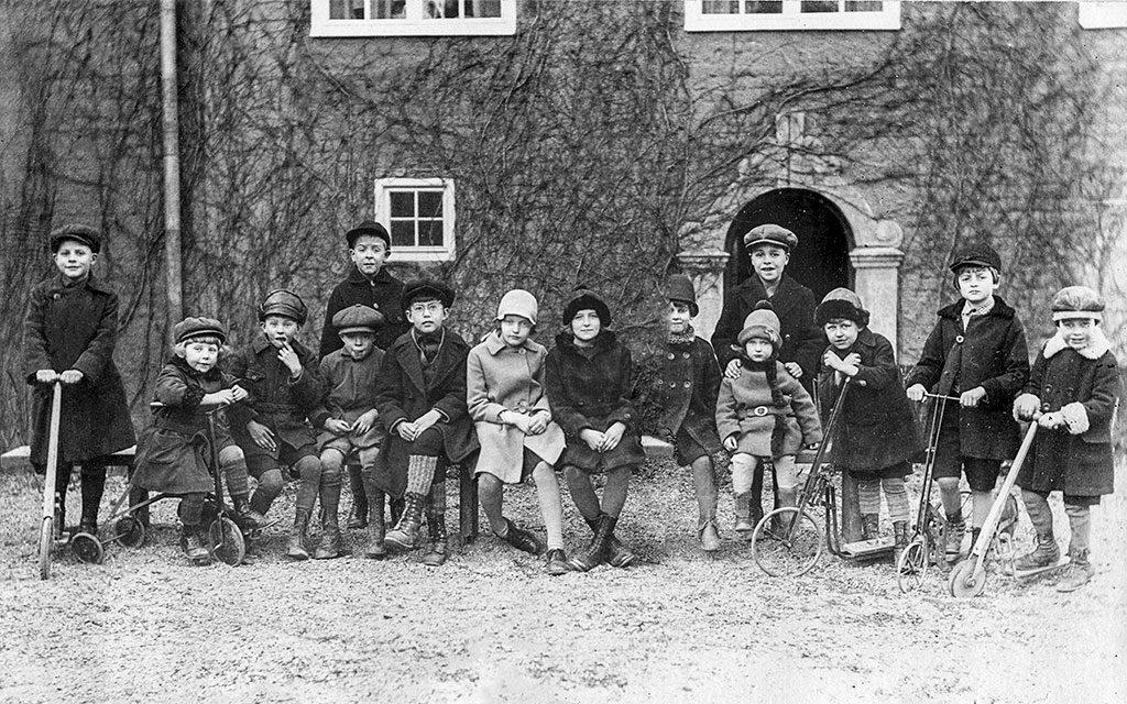 svartvitt foto på barn i lång rad på en innergård