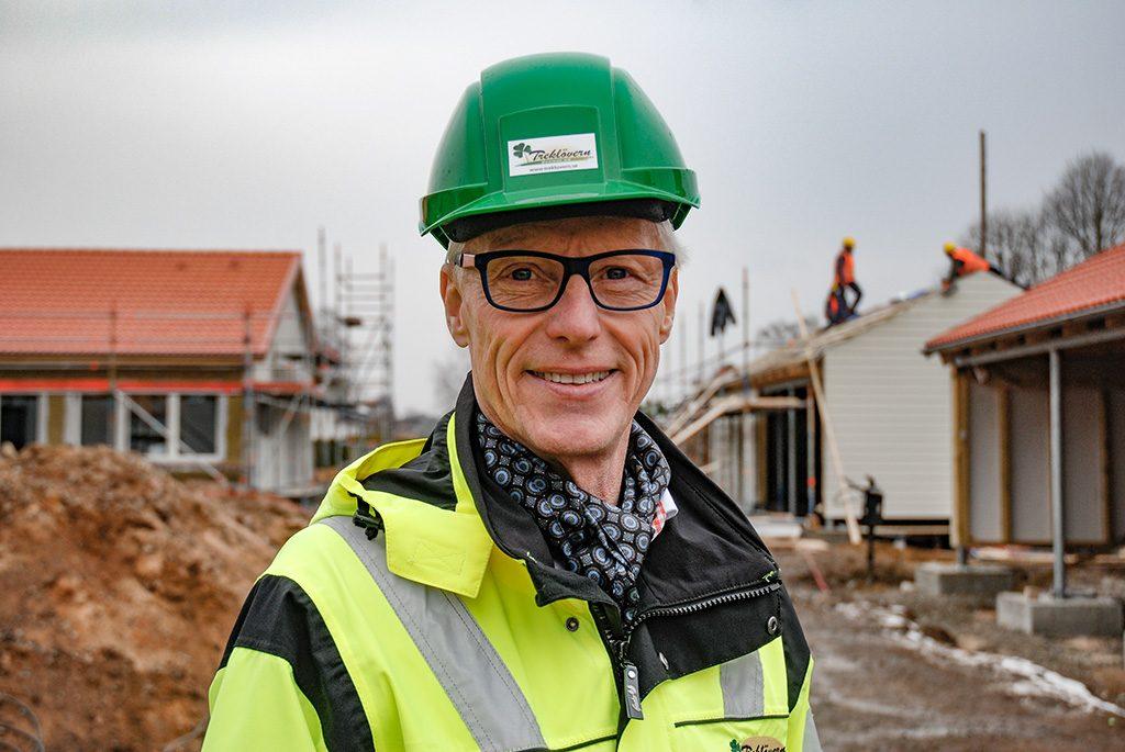 Äldre glad man i varselväst med grön bygghjälm på huvudet