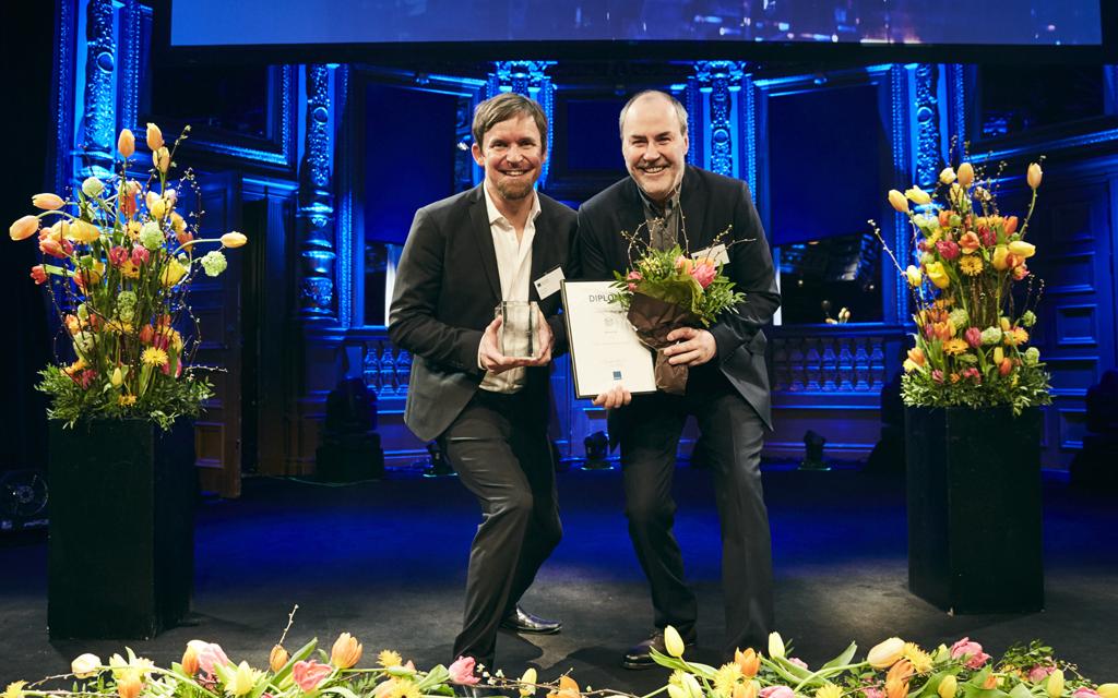 Två mycket glada män på scen i kvällsbelysning, med tulpaner och diplom