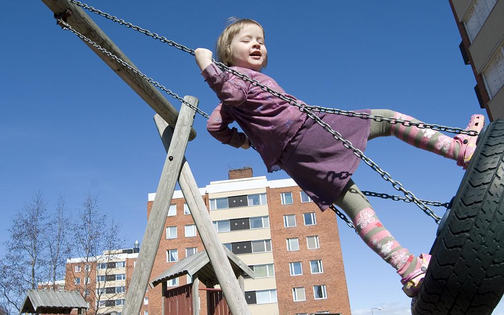 Flicka står på gunga och gungar högt upp i luften. I bakgrunden syns flerbostadshus.
