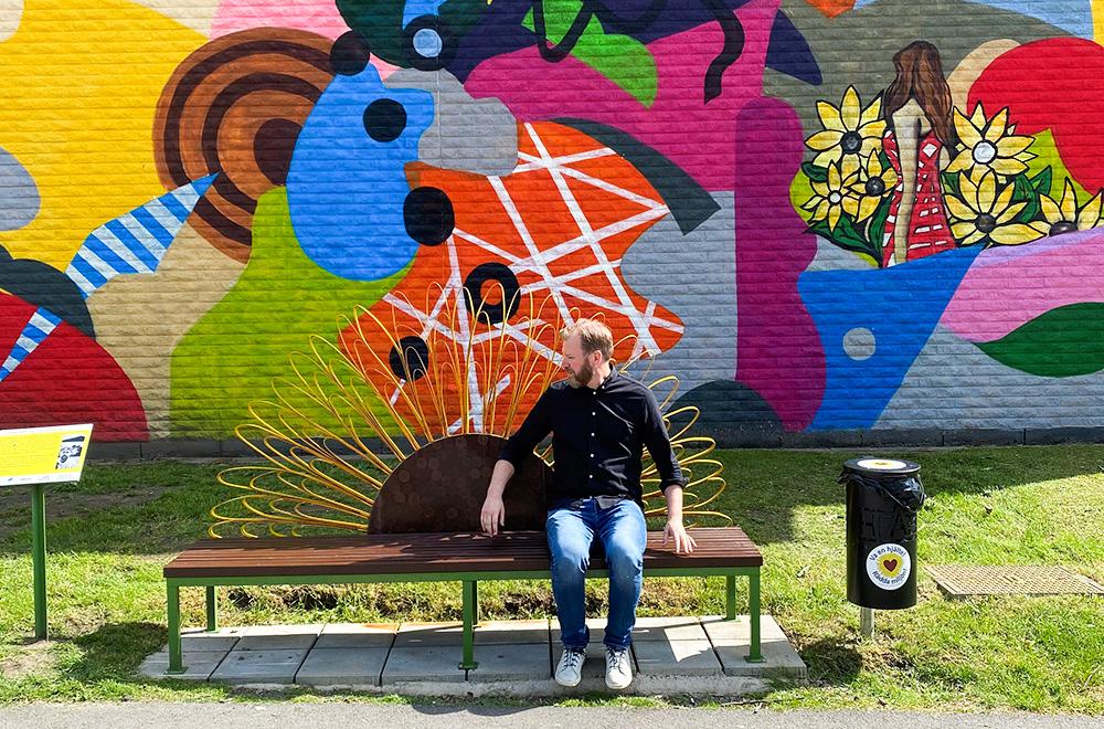 En man sitter på en bänk som har en solros i metall som ryggstöd. Bakom bänken finns en målad vägg i många färger med abstrakta mönster.