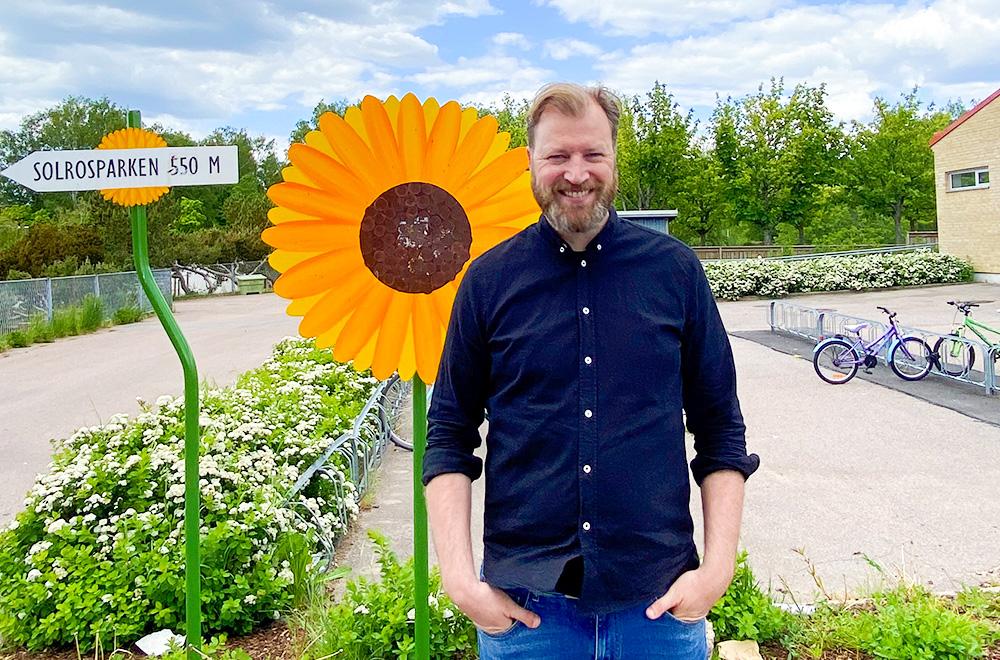 En man står i halvfigur framför en stor solros i plåtmaterial. Han ler och det är blå sommarhimmel i bakgrunden.