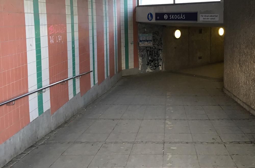 En mörk tunnel som leder till en pendeltågsstation. Betongplattor på marken och kakelklädda väggar i orange, grönt och vitt.