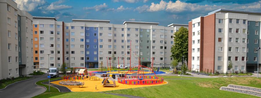 Höghus med färgglad lekplats i förgrunden.