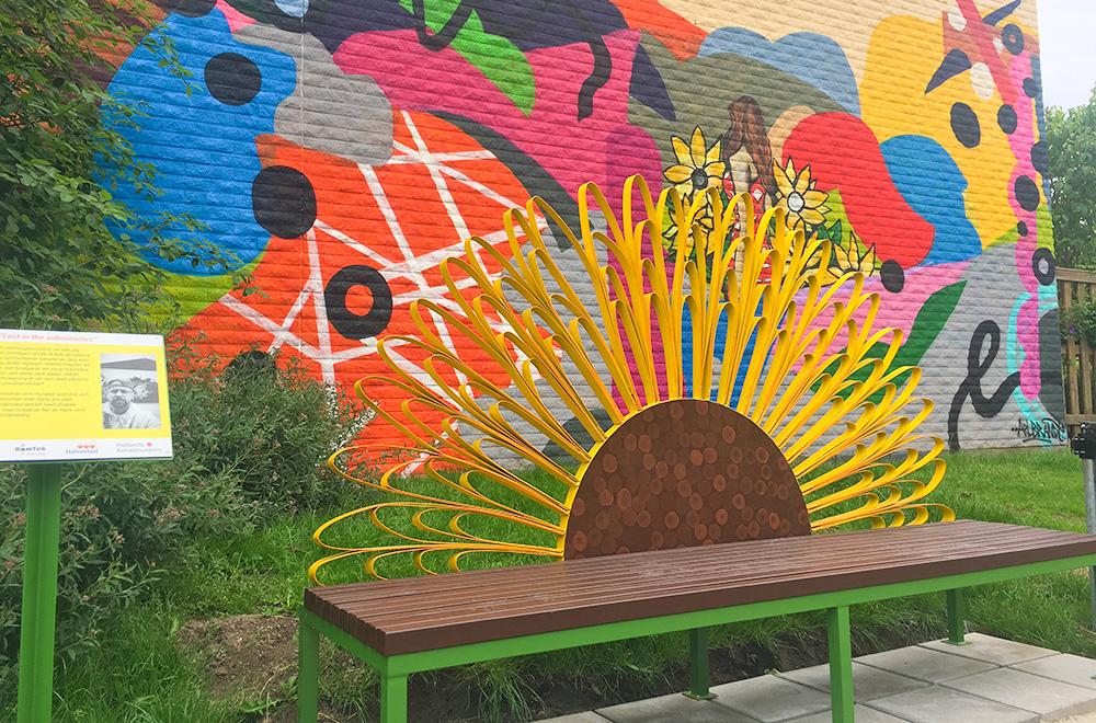Bänk med ryggstöd i metall i form av en solros. Bakom bänken finns en färgglad vägg målad i abstrakta mönster.