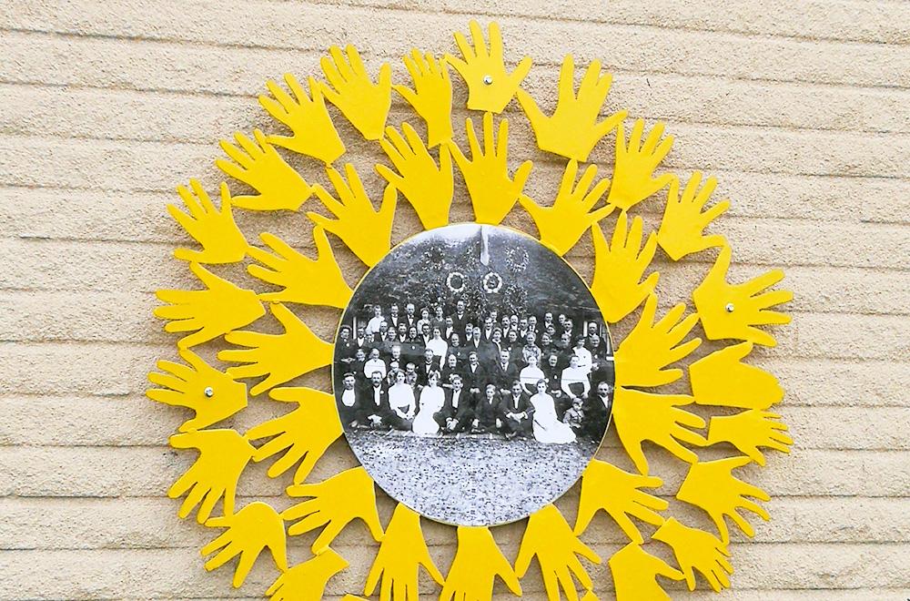 Ett svartvitt foto omgärdas av mängder av handflator i metall, som tillsammans bildar en gul ram runt fotot. Hela konstverket sitter utomhus på en vit tegelvägg.