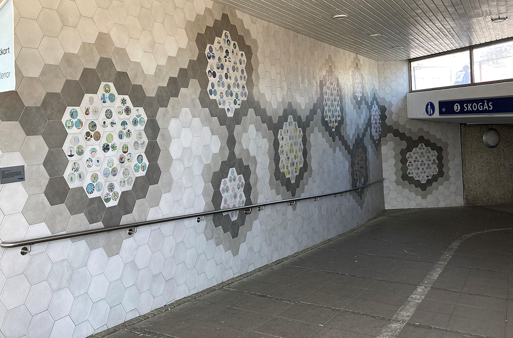 Gångtunnel med kakeldekorationer med barnteckningar. Tunneln leder till en pendeltågsstation.
