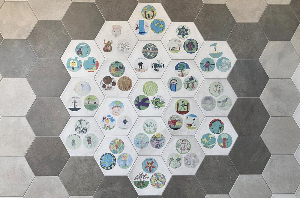 Närbild på några av de keramiska plattorna med barnens alster.