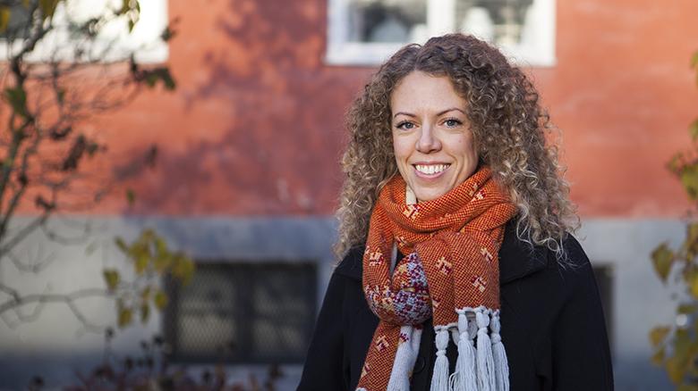 Leende kvinna med halvlångt lockigt hår och orangemönstrad halsduk runt halsen. Står framför fasaden av ett varmrött hus.