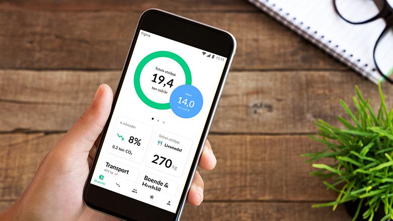 Mobiltelefon som hålls i en hand. På skärmen syns siffror och diagram som visar koldioxidutsläpp.