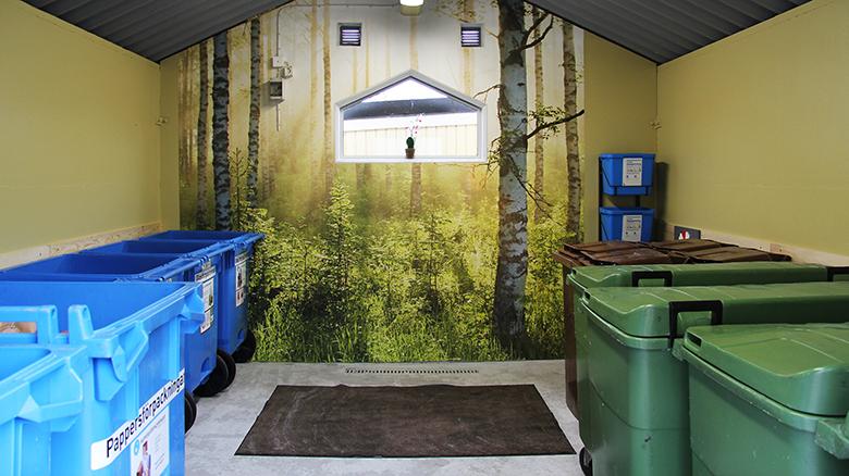 Sopsorteringsrum med stora kärl och en fondvägg med solbelysta björkar.