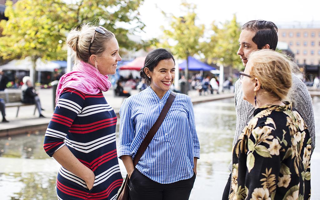Fyra personer står leende och pratar med varandra på en offentlig plats i en stad. De ler och det ser ut att vara en någorlunda varm dag.