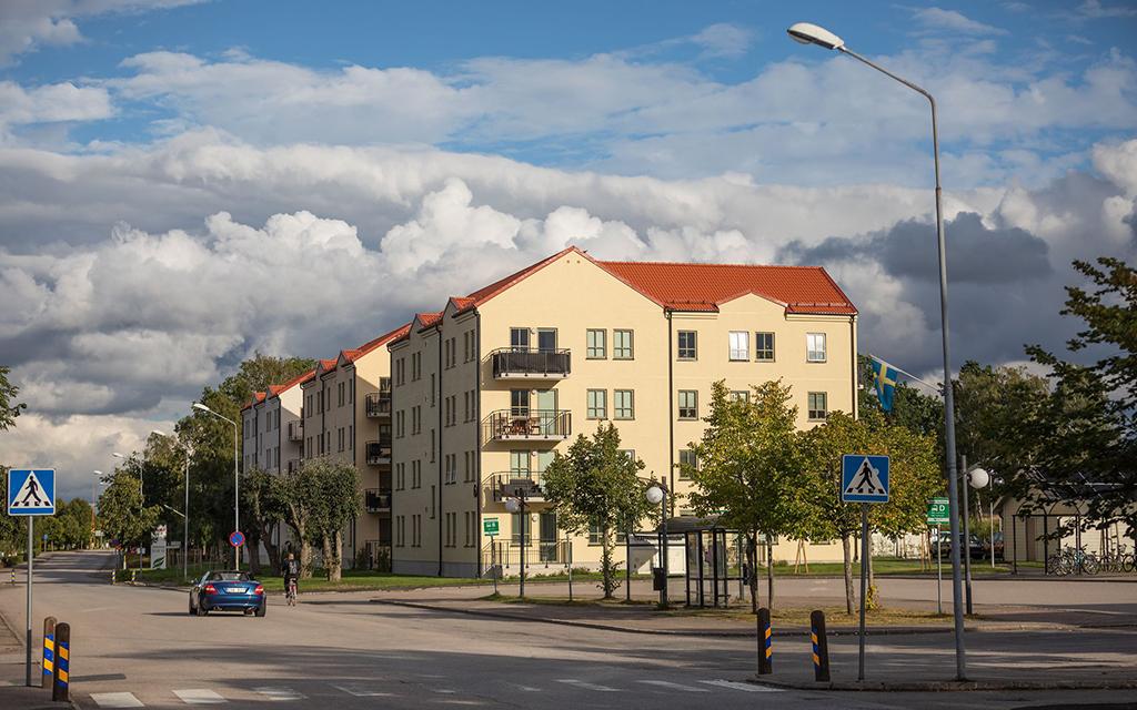 Flerbostadshus med fyravåningar och fasader i gul puts. Sol på husen, men tunga moln bortom hustaken.