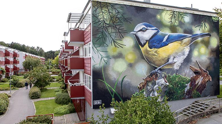 En mycket stor blåmes i klara färger är naturtroget målad på en fasad.
