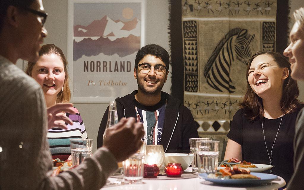 Fem unga människor sitter omkring ett matbord och skrattar och pratar.