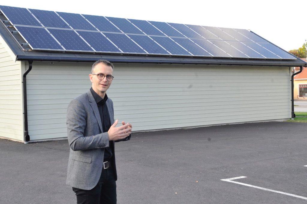 Leende man står framför uthus med solpaneler på taket.