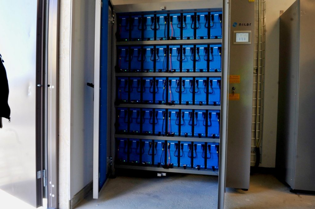 Ett öppet stort skåp med blå batterier på fem hyllplan.