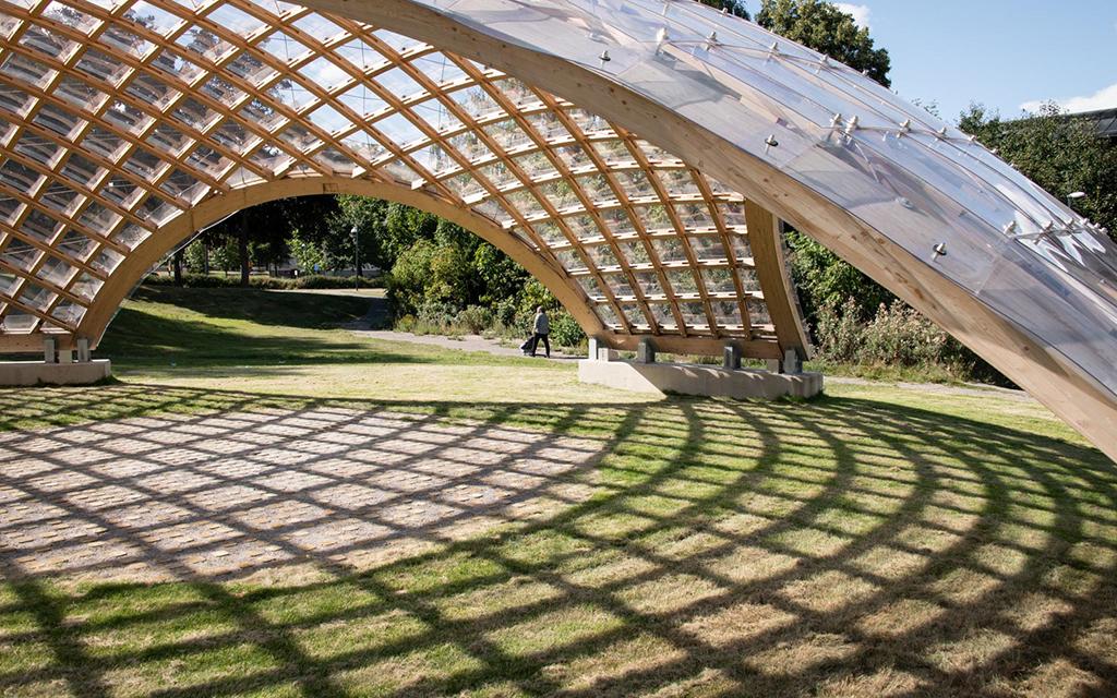 Ett tak som bildar ett regnskydd på en gräsmatta.
