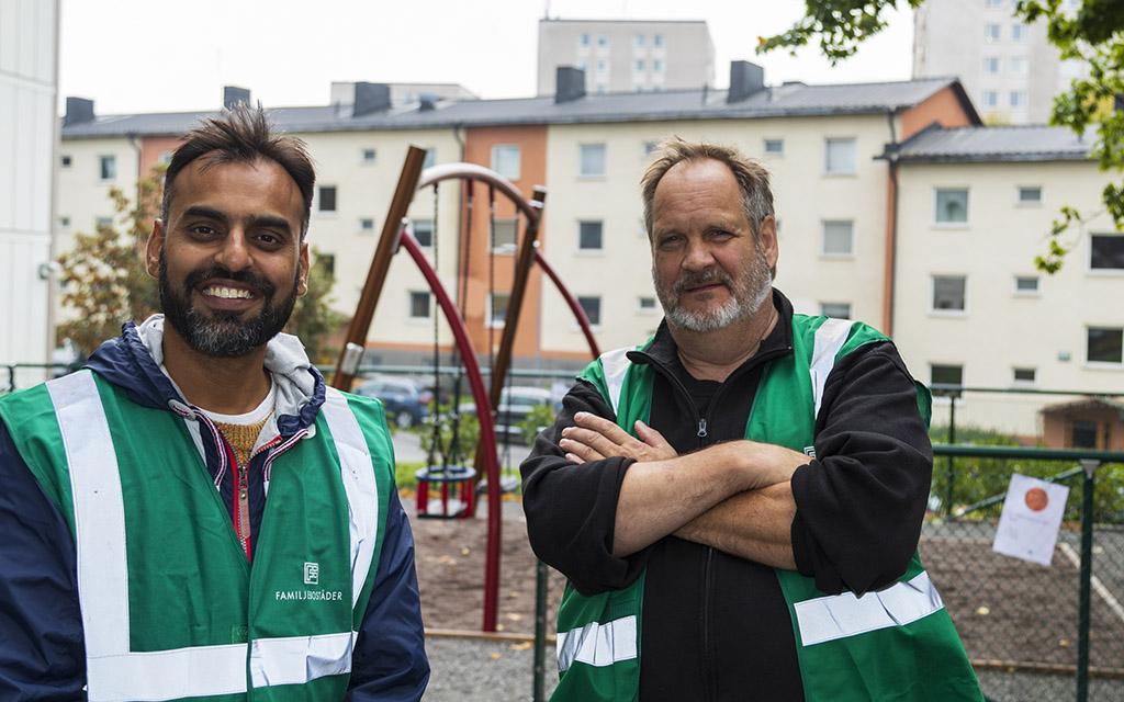 Två mån med arbetskläder på lekplats i förortsmiljö