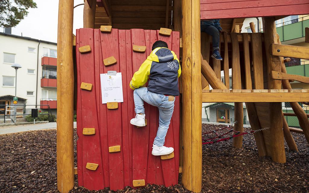 pojke som klättrar på klättervägg på lekplats i förortsmiljö