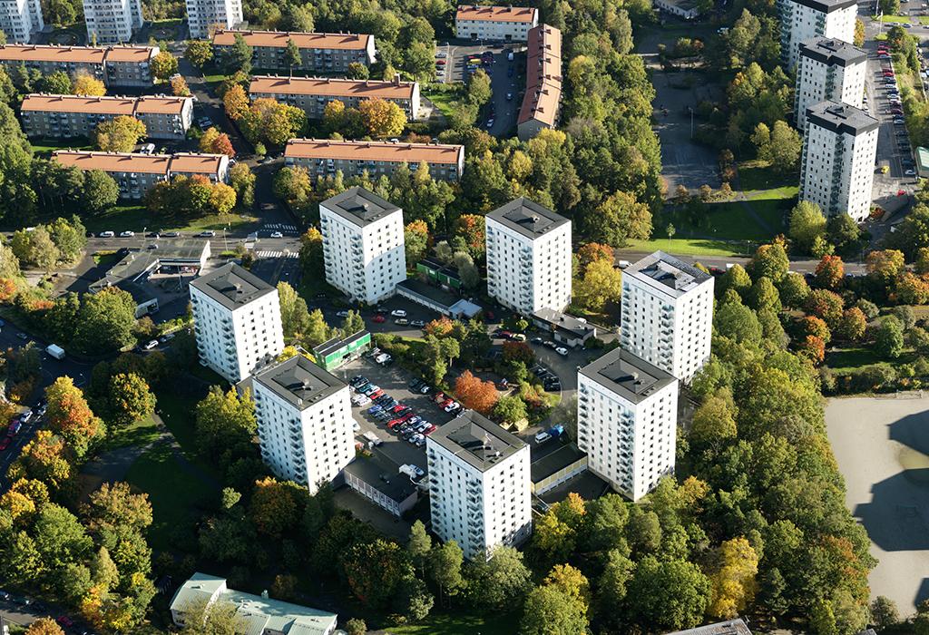 Flygfoto över med många flerbostadshus i grön förortsmiljö.