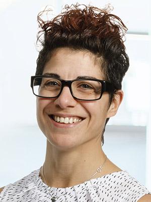 Porträttbild på kvinna med glasögon som tittar rakt in i kameran och ler.