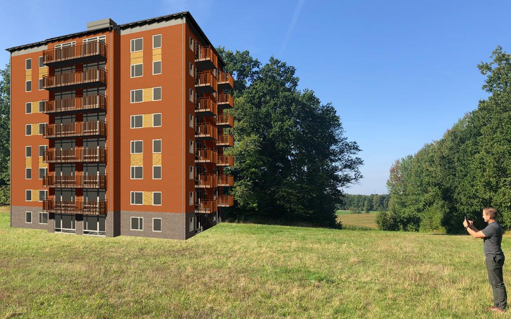 Man står på ett grönt fält och håller upp sin telefon mot ett brunt datagenererat åttavåningshus.