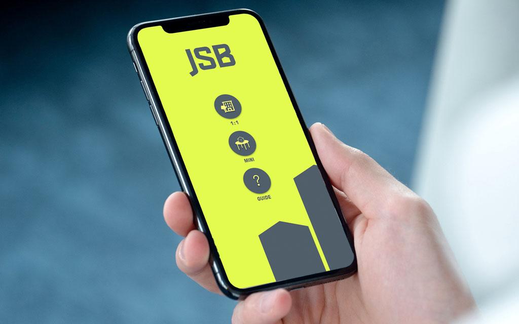 Hand håller i mobiltelefon med gul bakgrundsfärg texten JSB och flera symboler
