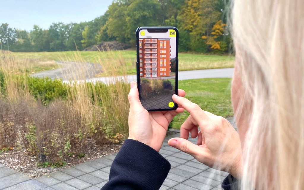 Tjej med ljust hår håller upp en mobiltelefon mot ett fält, i mobiltelefonen syns ett hus