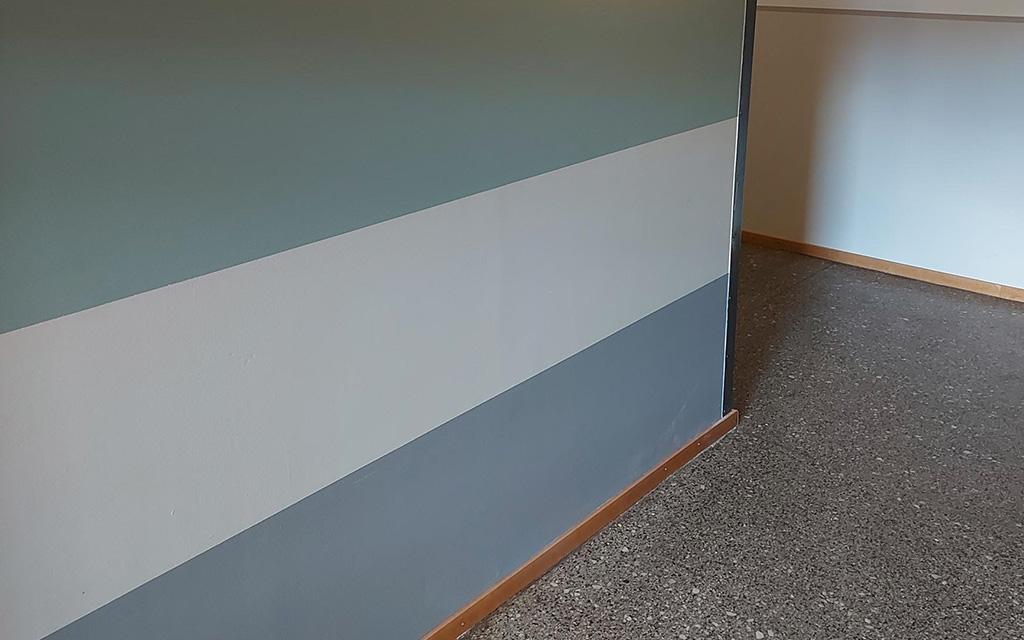 Vägg i flerbostadshusentré målad i flera olika färger